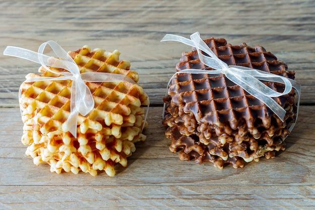 Deux tas de délicieuses gaufres belges au miel et chocolat sur table en bois.