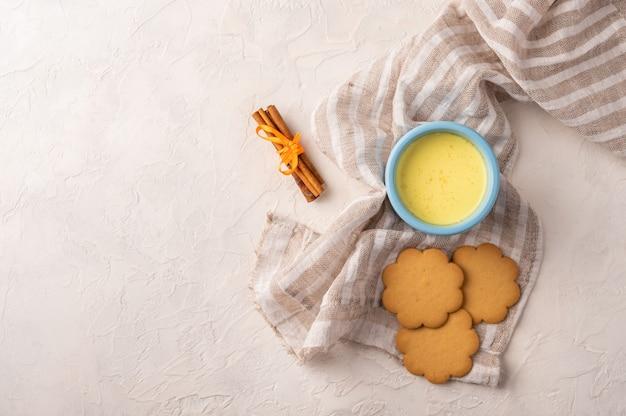 Deux tasse bleue avec du thé chai masala indien traditionnel, des bâtons de cannelle et des biscuits sur une serviette en lin