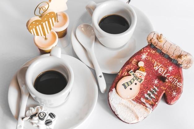 Deux tasse de café et un gant en bois avec texte de bienvenue et bonhomme de neige sur fond blanc