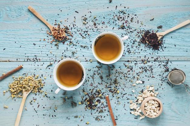 Deux tasse de thé dans un bol en céramique avec des fleurs de chrysanthème chinois séchées et des herbes sur la table