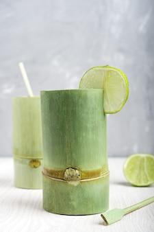 Deux tasses en bambou vert avec boisson rafraîchissante et tranches de citron vert sur table en bois blanc