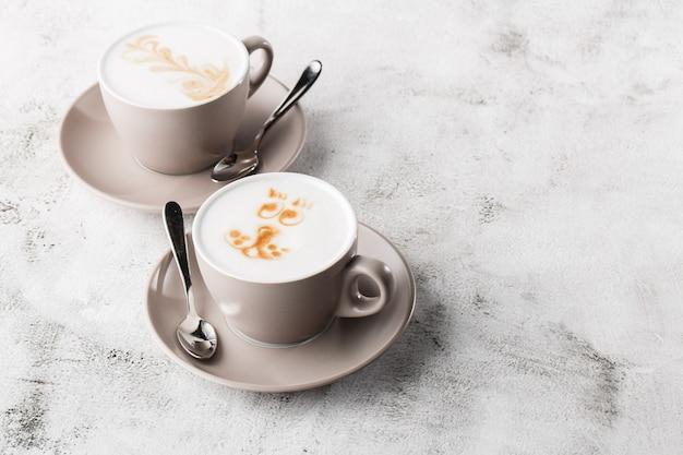 Deux tasses blanches de café latte chaud avec une belle texture d'art latte en mousse de lait isolé sur fond de marbre brillant. vue aérienne, espace copie. publicité pour le menu du café. menu du café. horizontal