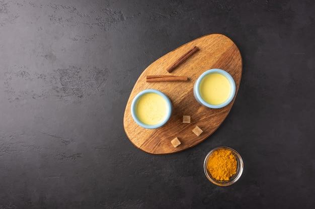 Deux tasses bleues en céramique avec du thé chai masala indien traditionnel avec du sucre sur une planche à découper