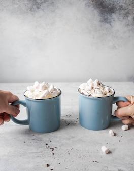 Deux tasses bleues avec du chocolat chaud, de la crème fouettée, des pépites de chocolat dans les mains de personnes incertaines sur fond gris