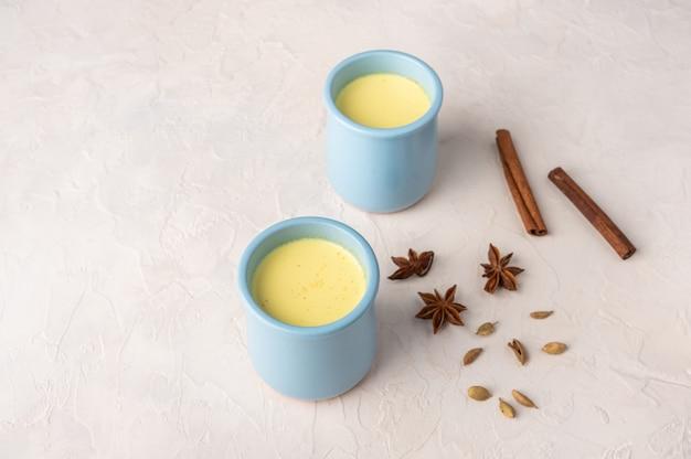 Deux tasses bleues avec du thé chai masala indien traditionnel avec des épices sur une serviette en lin