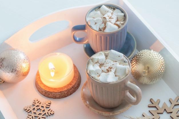 Deux tasses de boisson chaude avec des guimauves et un décor de noël sur un plateau en bois blanc