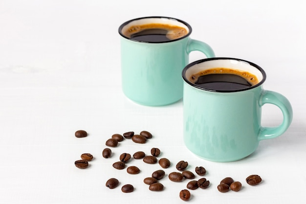 Deux tasses de café aromatique frais avec des grains sur une table en bois blanc