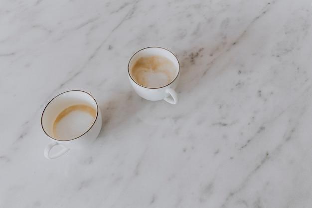 Deux tasses de café au lait sur une table de marbre