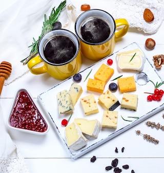 Deux tasses de café et divers morceaux de fromage