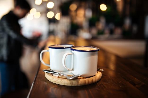Deux tasses avec café du matin sur une planche de bois
