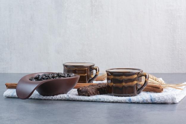 Deux tasses de café avec feuille de papier et chocolats sur nappe.