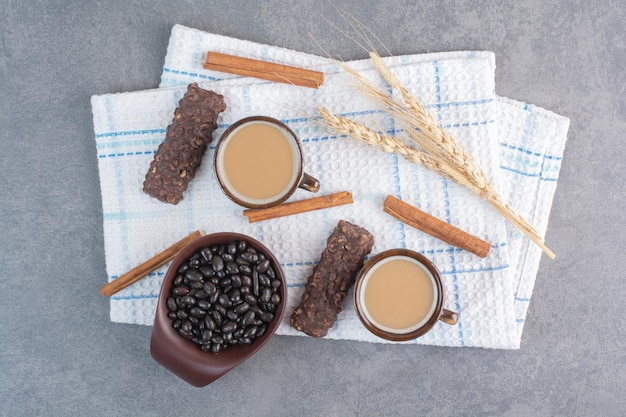 Deux tasses de café avec feuille de papier et chocolats sur nappe