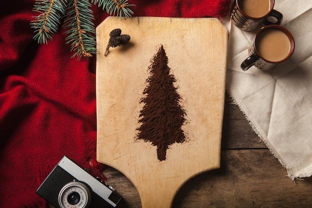 Les deux tasses de café sur fond de bois et arbre de noël fait de café moulu sur une planche à découper