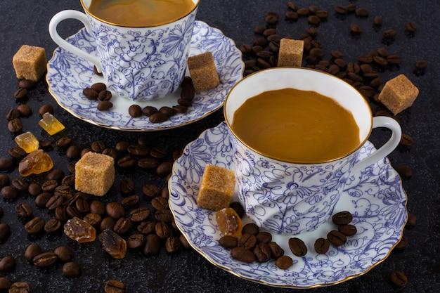Deux tasses à café et grains de café sur fond noir
