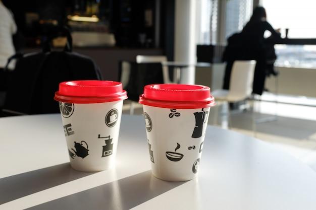 Deux tasses de café jetables sur la table du café.