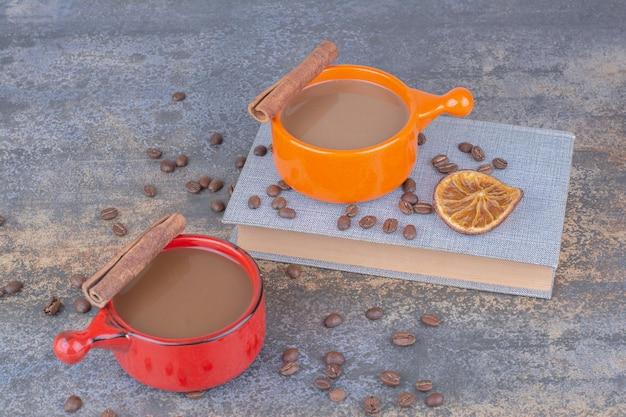 Deux tasses de café, livre et grains de café sur table en pierre. photo de haute qualité