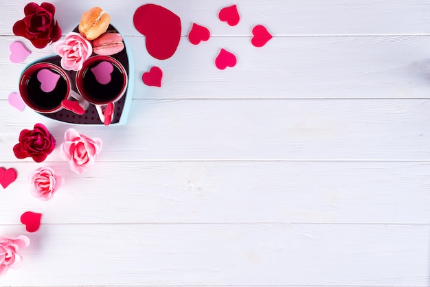 Deux tasses de café, des macarons, des fleurs dans une boîte en forme de cœur sur fond blanc.