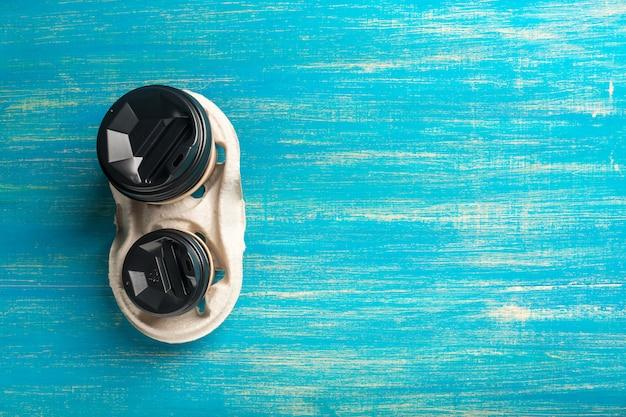 Deux tasses de café en papier jetables et un porte-gobelet jetable sur bleu