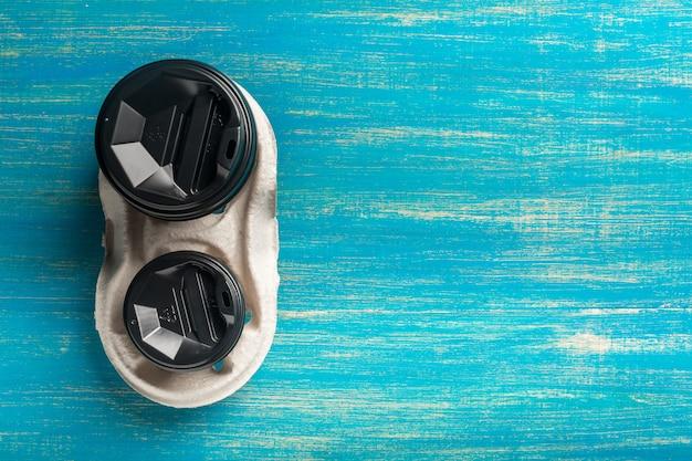 Deux tasses de café en papier jetables et un porte-gobelet jetable sur un bois bleu