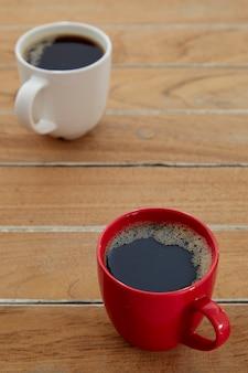 Deux tasses de café rouge et blanc sur bois