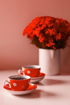 Deux tasses à café rouges sur fond blanc, pause-café et concept de dépendance à la caféine. fleurs rouges sur la table