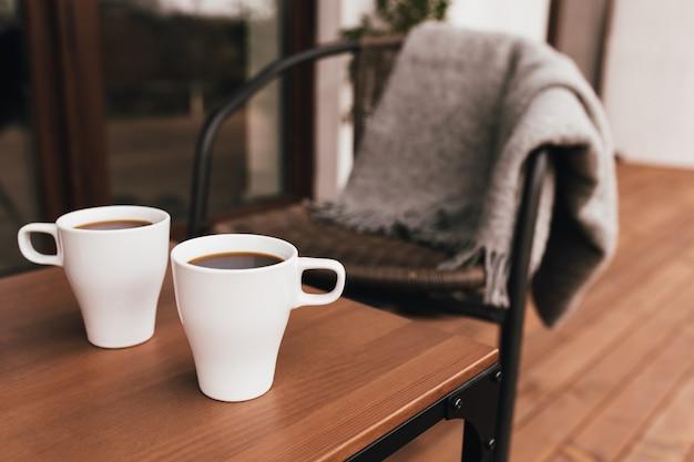 Deux tasses de café sur la table sur la terrasse en bois brun pendant le coucher du soleil du soir. détente, concept de vie à la campagne silencieuse. belles soirées en couple