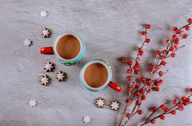 Deux tasses de café sur un tableau blanc avec une branche de fruits rouges