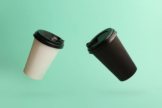 Deux tasses de café volantes sur le beau fond de menthe noir et blanc bicolore