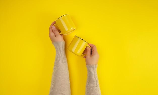 Deux tasses en céramique jaune sont soutenues par une main féminine jaune