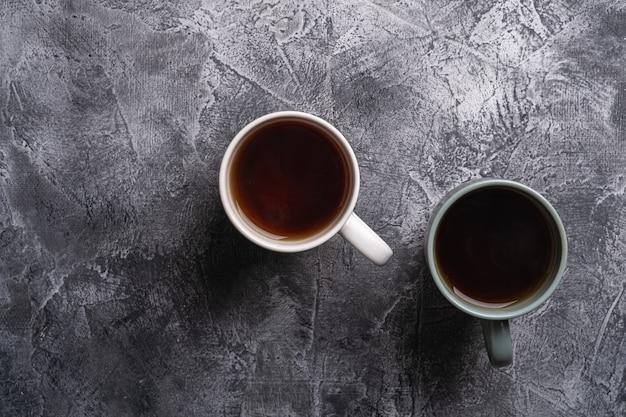 Deux tasses en céramique avec thé noir, boisson chaude en tasse blanche et grise sur fond de pierre sombre texturée, vue du dessus
