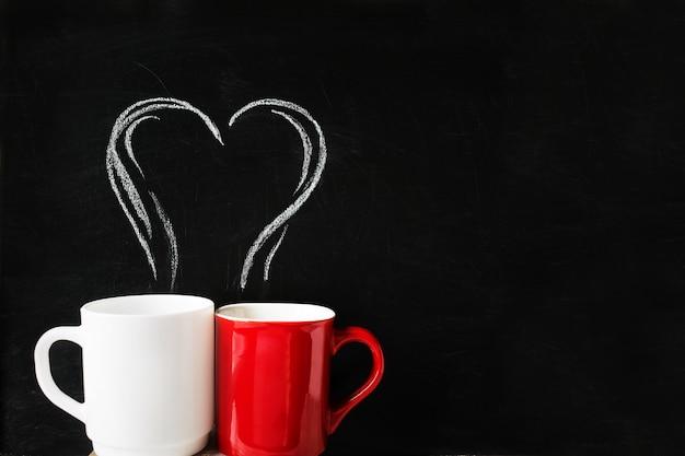Deux tasses avec coeur fumée dessiné à la craie sur tableau noir
