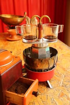 Deux tasses d'espresso en cours d'infusion avec une mini cafetière rétro avec un moulin en premier plan