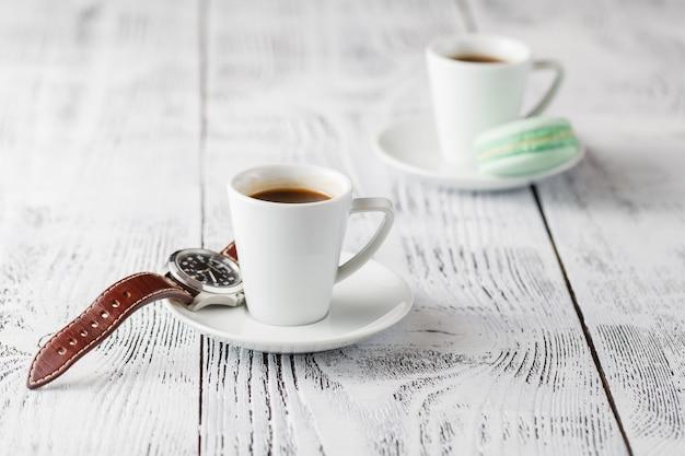 Deux tasses d'expresso sur une table en bois blanc.