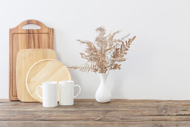 Deux tasses et fleurs séchées sur cuisine blanche