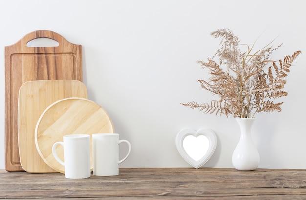 Deux tasses et fleurs séchées dans la cuisine blanche