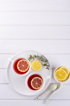 Deux tasses de fruits rouges et tisane avec une tranche de citron, vue du dessus