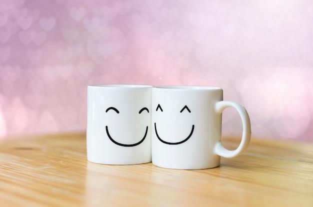 Deux tasses heureux sur la table en bois avec fond de bokeh coeurs saint valentin