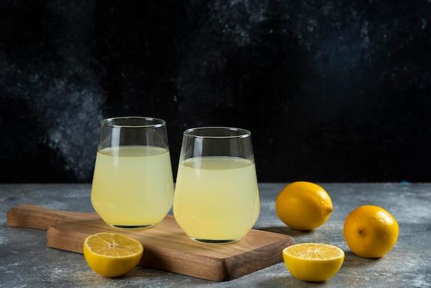 Deux tasses de jus de citron sur planche de bois.