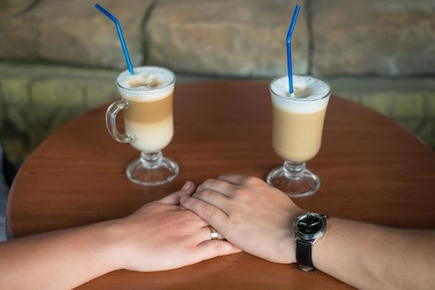 Deux tasses de latte et un couple main dans la main