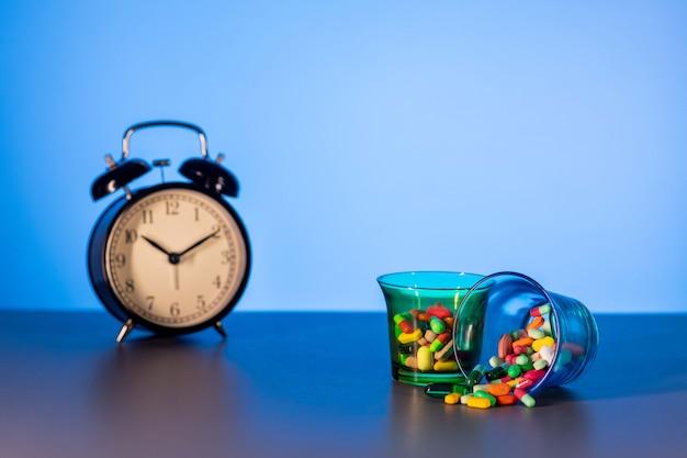 Deux tasses à mesurer avec des médicaments dispersés à côté d'un réveil noir vintage. le concept du temps qui passe.