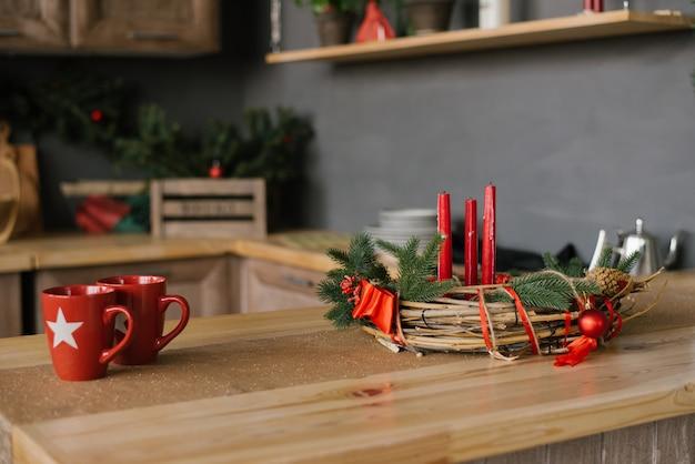 Deux tasses rouges et une guirlande de noël avec des bougies sur la table, décor de maison de vacances