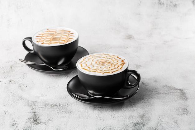 Deux tasses sombres de café avec texture art latte caramel au lait isolé sur fond de marbre brillant. vue aérienne, espace copie. publicité pour le menu du café. menu du café. photo horizontale.