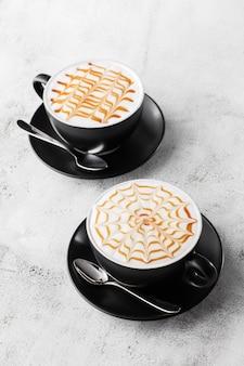 Deux tasses sombres de café avec texture art latte caramel au lait isolé sur fond de marbre brillant. vue aérienne, espace copie. publicité pour le menu du café. menu du café. photo verticale.