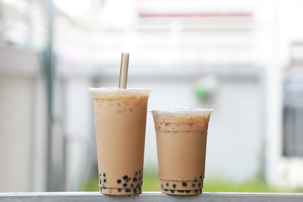 Deux tasses de thé au lait glacé, grand et petit, avec une boisson fraîche et sucrée à bulles boba style taiwan mis sur la barre d'acier et l'arrière-plan flou, concept de nourriture et de boisson