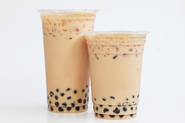 Deux tasses de thé au lait glacé grand et petit avec bulle boba style de taiwan sur fond blanc, boisson sucrée de glace fraîche isolée