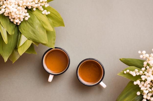 Deux tasses à thé et bouquets de muguet sur une table verte. pause pour se reposer, vie lente. vue de dessus