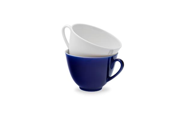 Deux tasses à thé en céramique blanche et bleu foncé. fond blanc isolé.