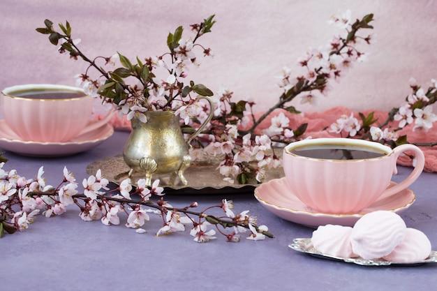 Deux tasses de thé dans des plats roses, meringues et fleurs de cerisier dans un vieux vase - heure du thé