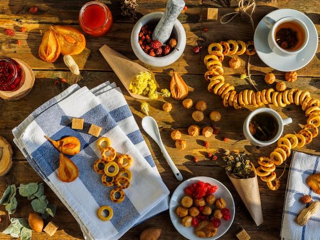Deux tasses de thé, diverses confitures et autres bonbons sur la vieille table en bois.