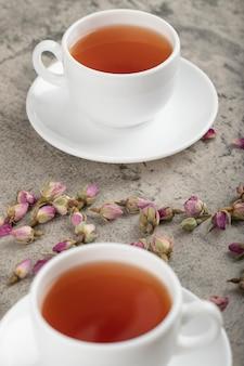 Deux tasses de thé noir avec des roses séchées sur la surface de la pierre.